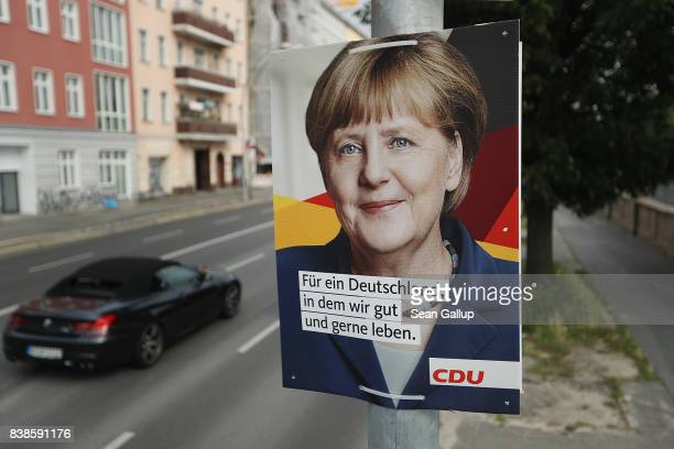 Cars drive past an election campaign poster that depicts German Chancellor and Christian Democrat Angela Merkel on August 24 2017 in Berlin Germany...