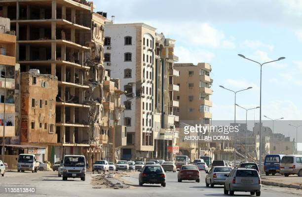 Cars drive past buildings heavily damaged from previous clashes in Libya's eastern city of Benghazi on April 8 2019 Vowing to cleanse the country of...