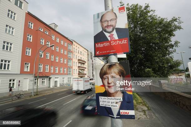Cars drive past election campaign posters that depict German Social Democrat and chancellor candidate Martin Schulz and German Chancellor and...