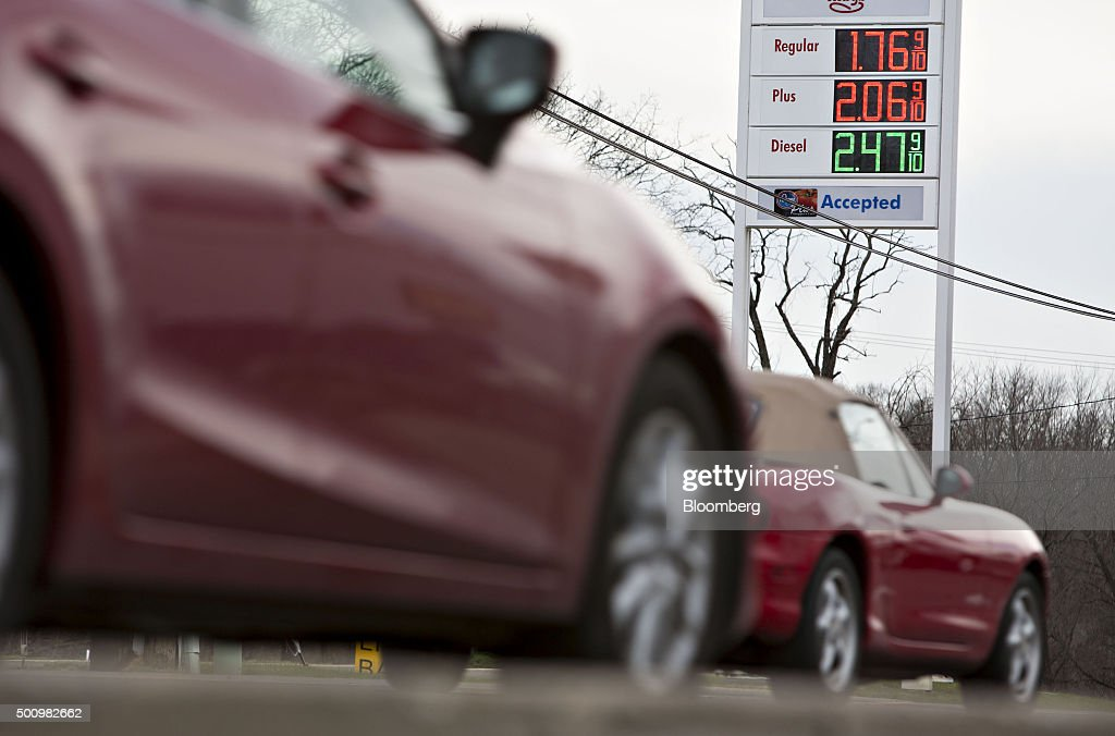 Cars drive past gas prices displayed on a sign outside a fueling station in Chilicothe, Illinois, U.S., on Friday, Dec. 11, 2015. The cost of a gallon of regular gasoline fell 6.7 percent last month, based on data from motoring group AAA. Photographer: Daniel Acker/Bloomberg via Getty Images