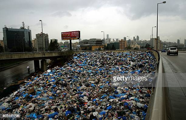 Cars drive past rubbish piled up next to a highway bridge at the eastern entrance to the Lebanese capital Beirut on January 5 2016 AFP PHOTO/JOSEPH...