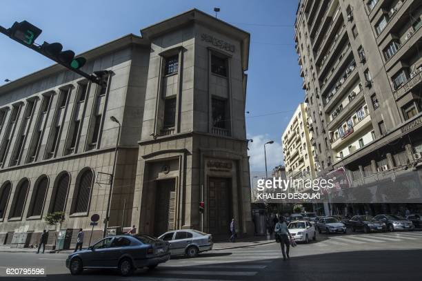 Cars drive past the Egyptian Central Bank in downtown Cairo on November 3 2016 Egypt floated the country's pound as part of a raft of reforms after a...