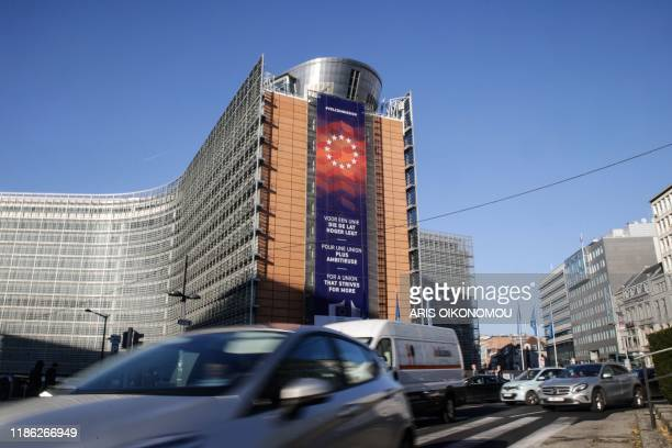 Cars drive past the European Commission headquarters with a new banner with the lettering reading 'For a union that strives for more' in different...