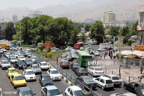 Cars drive through a busy road in the Iranian capital Tehran on July 3 2019 The Iranian economy is struggling in part because of the crippling US...