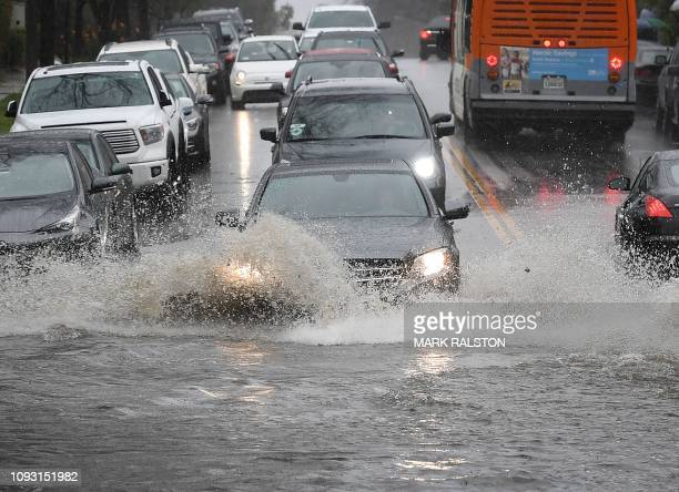 Cars drive through a flooded street after a storm dumped heavy rain on Los Angeles California on February 2 The city is enduring three backtoback...