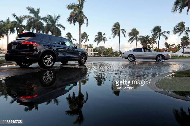 Cars drive through and around water pooling at the intersection of East Las Olas Boulevard and Coral Way in Fort Lauderdale Fla on Friday Oct 25 2019