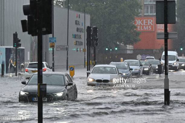 Cars drive through deep water on a flooded road in The Nine Elms district of London on July 25, 2021 during heavy rain. - Buses and cars were left...