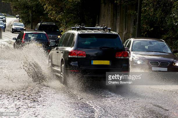 Cars drive through flood puddles creating splashes