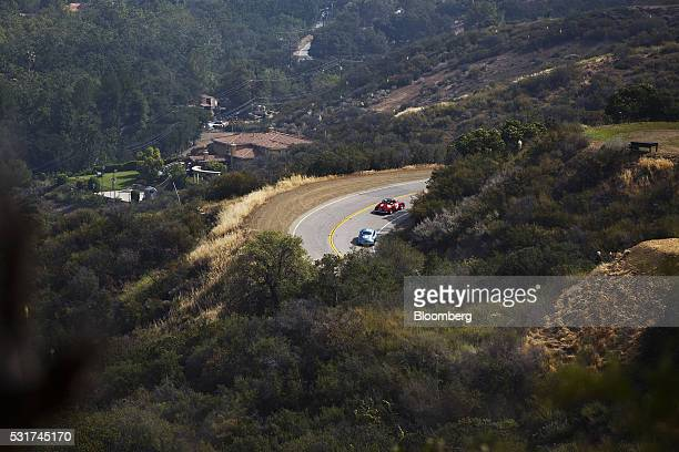 Cars drive through Mulholland Highway during the Friends of Steve McQueen Car Show Rally from Malibu to Santa Barbara California US on Saturday May...