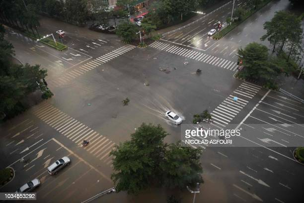Cars drive through partially flooded streets a day after super Typhoon Mangkhut in Yangjiang in Guangdong province on September 17 2018 Typhoon...