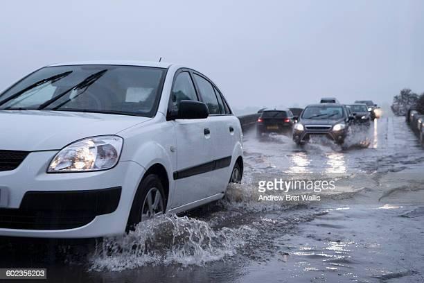 Cars drive through road bridge flood water