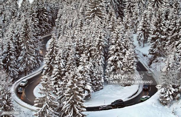 Cars drive through the snowy landscape on a serpentine mountain pass road near Oberjoch southern Germany on December 29 2017 / AFP PHOTO / dpa /...