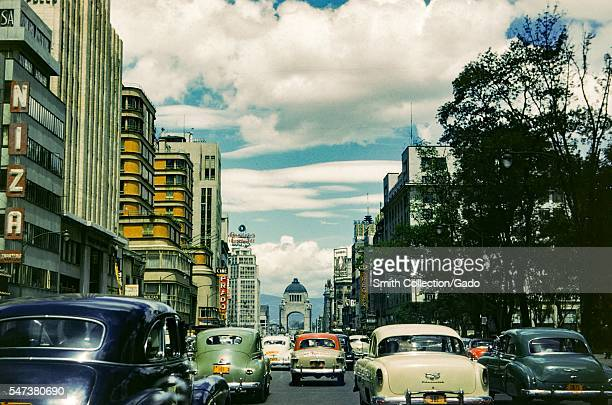 Cars drive through the streets of Mexico City with Cine Prado the Hotel Regis and several advertising signs visible Mexico City Mexico 1952