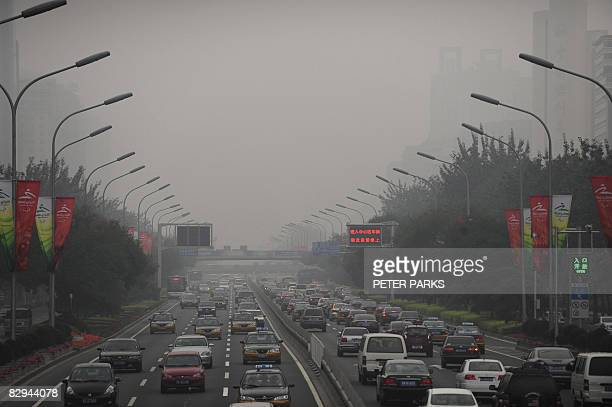 Cars drive through thick smog on a street in Beijing on September 21 the first day of no traffic restrictions which limited motorists with even or...