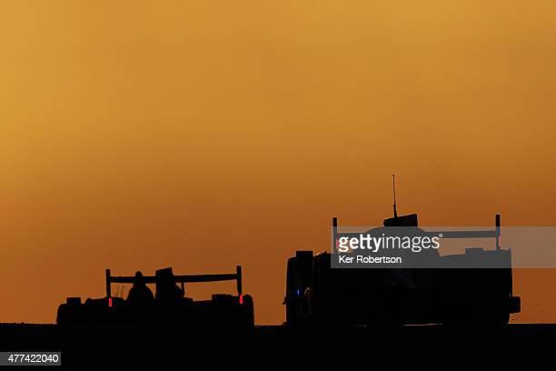 Cars drive under the Dunlop Bridge at sunrise during the Le Mans 24 Hour race at the Circuit de la Sarthe on June 14 2015 in Le Mans France