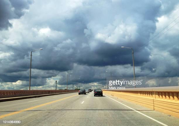 Cars driving along bridge toward stormy sky