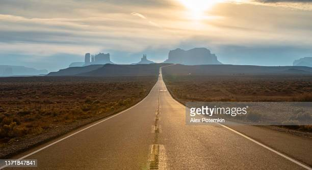 cars driving on a highway in monument valley, new mexico, usa - native american reservation stock pictures, royalty-free photos & images