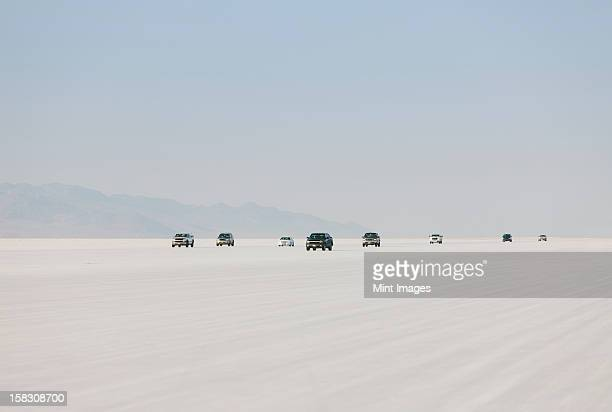 cars driving on bonneville salt flats during speed week. dusk. - bonneville salt flats stock photos and pictures