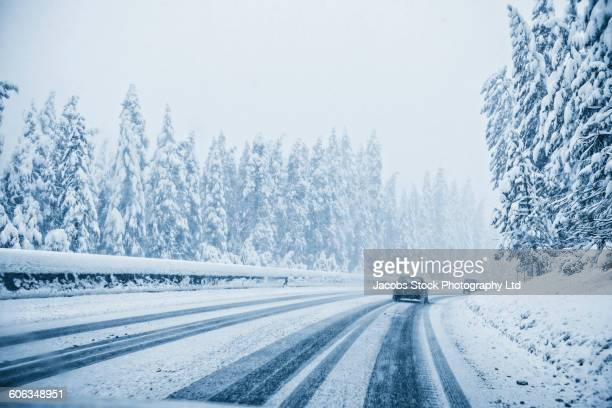 cars driving on snowy remote road - driving in snow stock photos and pictures
