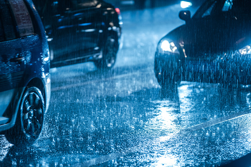 Cars driving on wet road in the rain with headlights 902497530