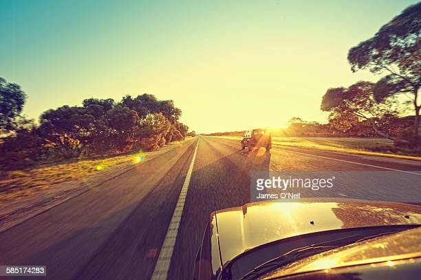 cars driving towards the sun on highway - travel stock pictures, royalty-free photos & images