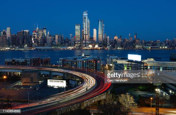 Cars enter and exit the Lincoln Tunnel in New Jersey as the sun sets on the skyline of midtown Manhattan in New York City on April 6 2019 as seen...