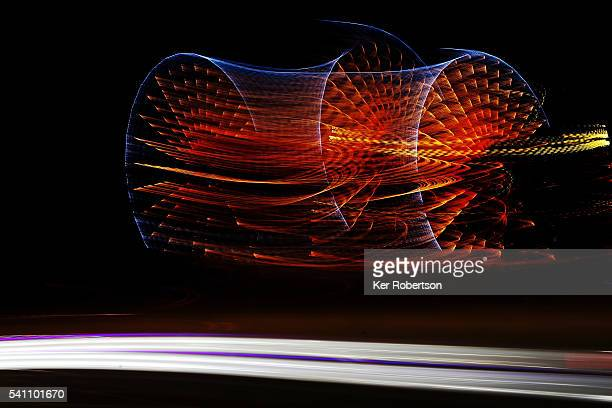 Cars go past the ferris wheel at night during the Le Mans 24 Hour race at the Circuit de la Sarthe on June 18 2016 in Le Mans France
