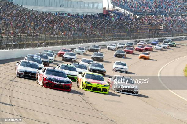 Cars go three wide led by NASCAR Xfinity Series driver Christopher Bell into turn one during the NASCAR Xfinity Series US Cellular 250 on July 27 at...