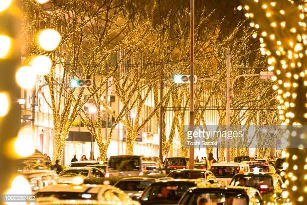 cars go through among the illuminated tree lined omotesadndo street in the night for winter holydays season at kitaaoyama, minato tokyo japan on december 06 2017 - 表参道 ストックフォトと画像