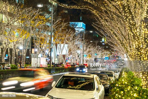 cars go through among the illuminated tree lined omotesadndo street for winter holydays season in the night at jingumae, shibuya tokyo japan on december 05 2017. - 表参道 ストックフォトと画像