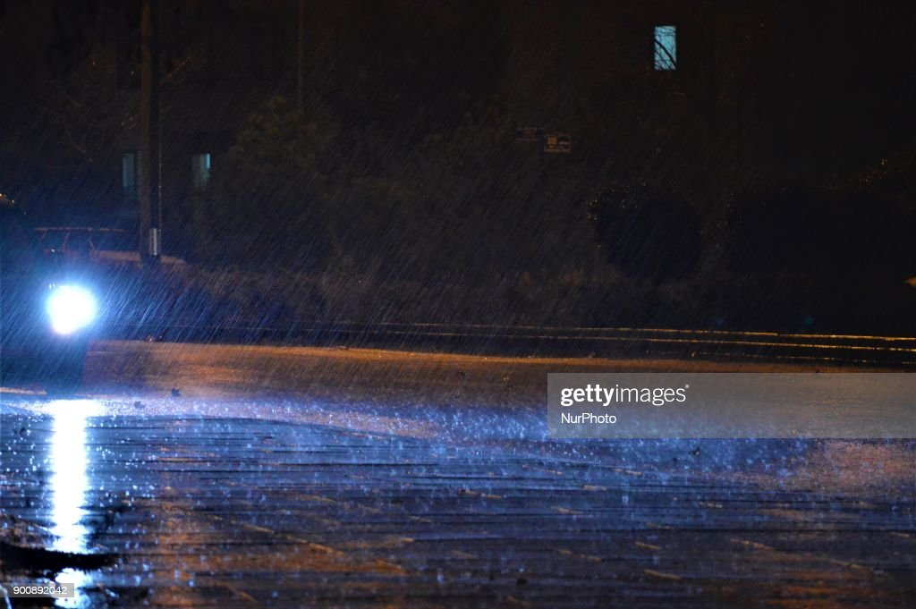 A car's headlights illuminate rain drops on a rain-drenched road as heavy rain falls in the winter season in Ankara, Turkey on January 3, 2018.