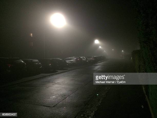 cars in parking lot by illuminated empty road at night - empty lot night stock pictures, royalty-free photos & images