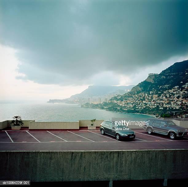 cars in parking lot with monaco harbour - モナコ公国 ストックフォトと画像