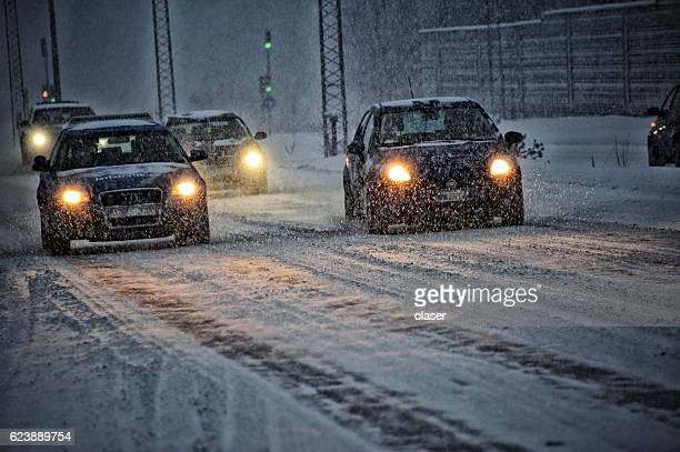 Cars in traffic, snowstorm and evening