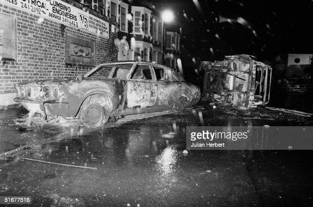 Cars left overturned and burnedout in the street after rioting on the Broadwater Farm housing estate Tottenham London 6th October 1985 The racial...