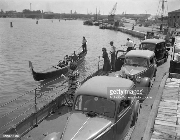 Cars line by the canal waiting to enter the Autorimessa Piazzale Roma garage Venice circa 1950