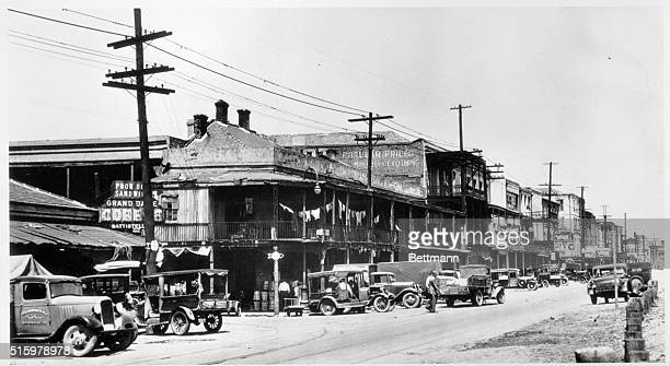 Cars line the street beside the soontoberemodeled shops of the French Market in New Orleans Louisiana May 1936