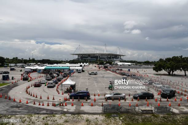 Cars line up at a rapid antigen coronavirus testing site at Hard Rock Stadium in Miami Gardens near Miami, on August 5, 2020. - In one of two...