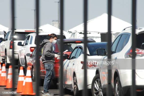 Cars line up for COVID19 testing at a drivethrough test site set up in the parking lot of Citizen Bank Park in South Philadelphia on March 26 2020