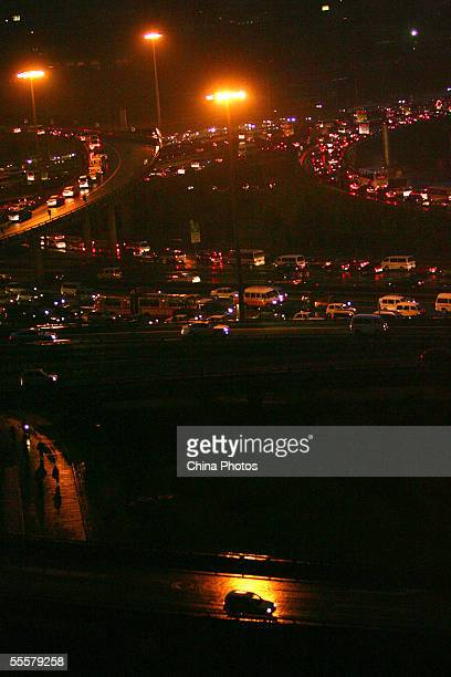 Cars line up on roads during a traffic jam at a cloverleaf junction on September 15 2005 in Beijing China According to state media Beijing has...