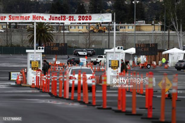 Cars line up to enter a coronavirus drive-thru test clinic at the San Mateo County Event Center on March 16, 2020 in San Mateo, California....