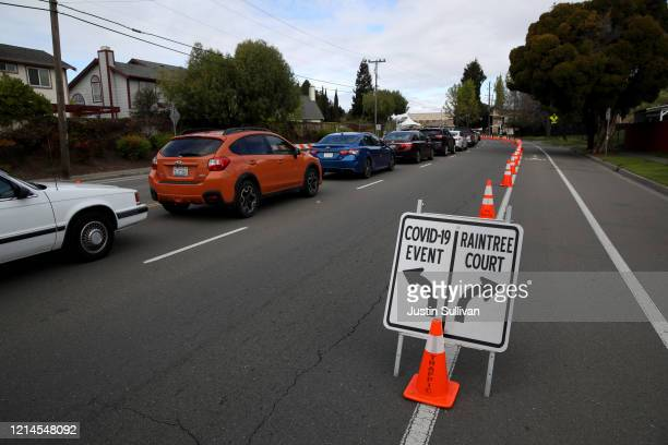 Cars line up to get a COVID19 test at a free public testing station on March 24 2020 in Hayward California Hundreds of people are lining up to...