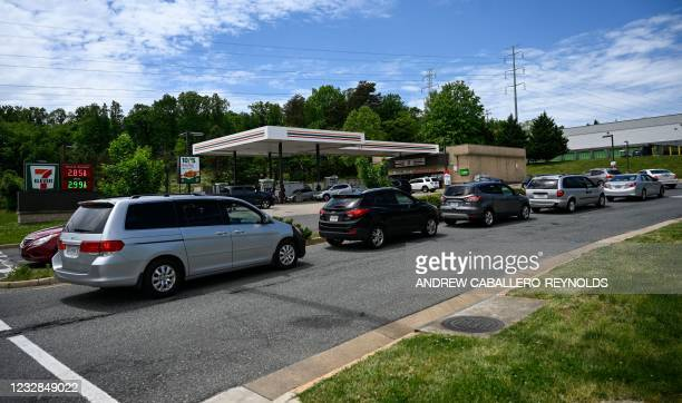 Cars line up to get gas at one of the few stations remaining open at a 7 Eleven station in Woodbridge, Virginia, on May 12, 2021. - Fears the...