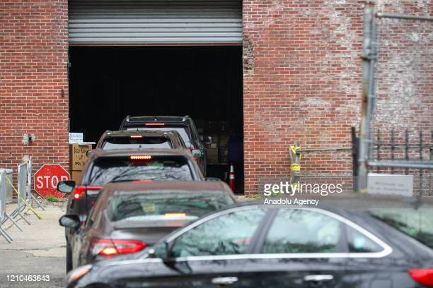 Cars lined up to get food supplies from the Kingsbridge Armory which has been used as a temporary food aid distribution center due to COVID-19...