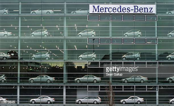 Cars made by German automotive maker Mercedes-Benz line the multi-story glass facade of the regional Mercedes-Benz headquarters January 16, 2003 in...