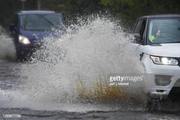 Cars make their way through flood water following torrential rain on the A760 road near to Lochwinnoch on August 2, 2020 in Lochwinnoch, Scotland....