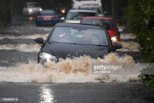 Cars make their way through flood water following torrential rain on the A760 road near to Lochwinnoch on August 4, 2020 in Lochwinnoch, Scotland....
