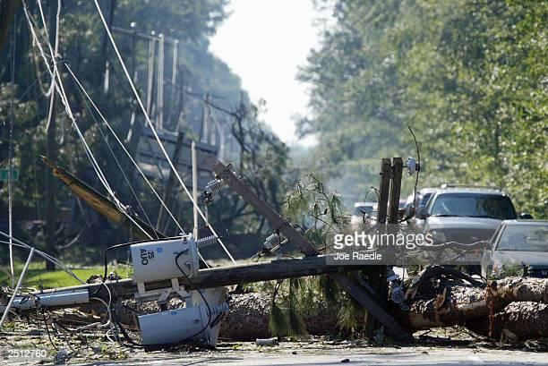 Cars maneuver around downed power lines after Hurricane Isabel passed through September 19 2003 in Poquoson Virginia Clean up continues in the region...