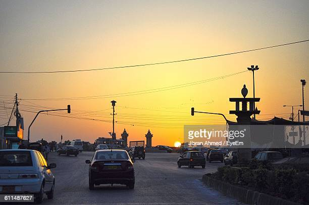 cars moving on road against clear sky at sunset - カラチ ストックフォトと画像