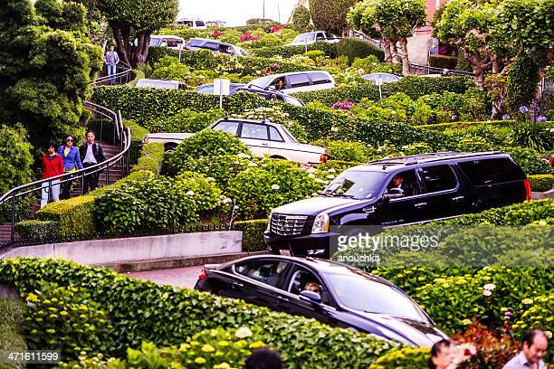 cars moving through famous lombard street, san francisco - lombard street san francisco stock pictures, royalty-free photos & images